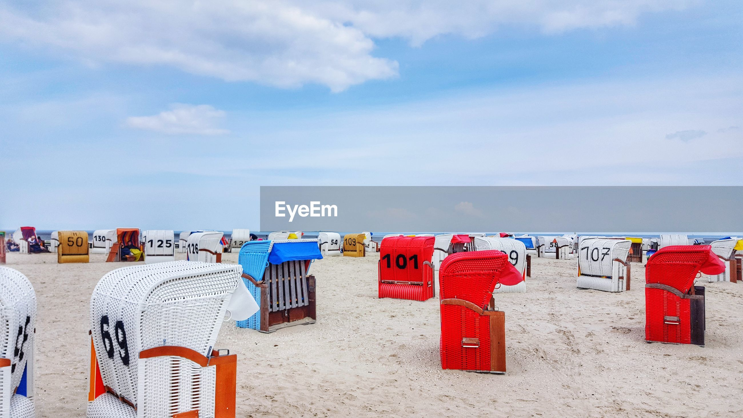 sand, beach, sky, cloud - sky, hooded beach chair, land, day, red, nature, no people, chair, seat, outdoors, security, water, protection, side by side, multi colored, safety, group of objects