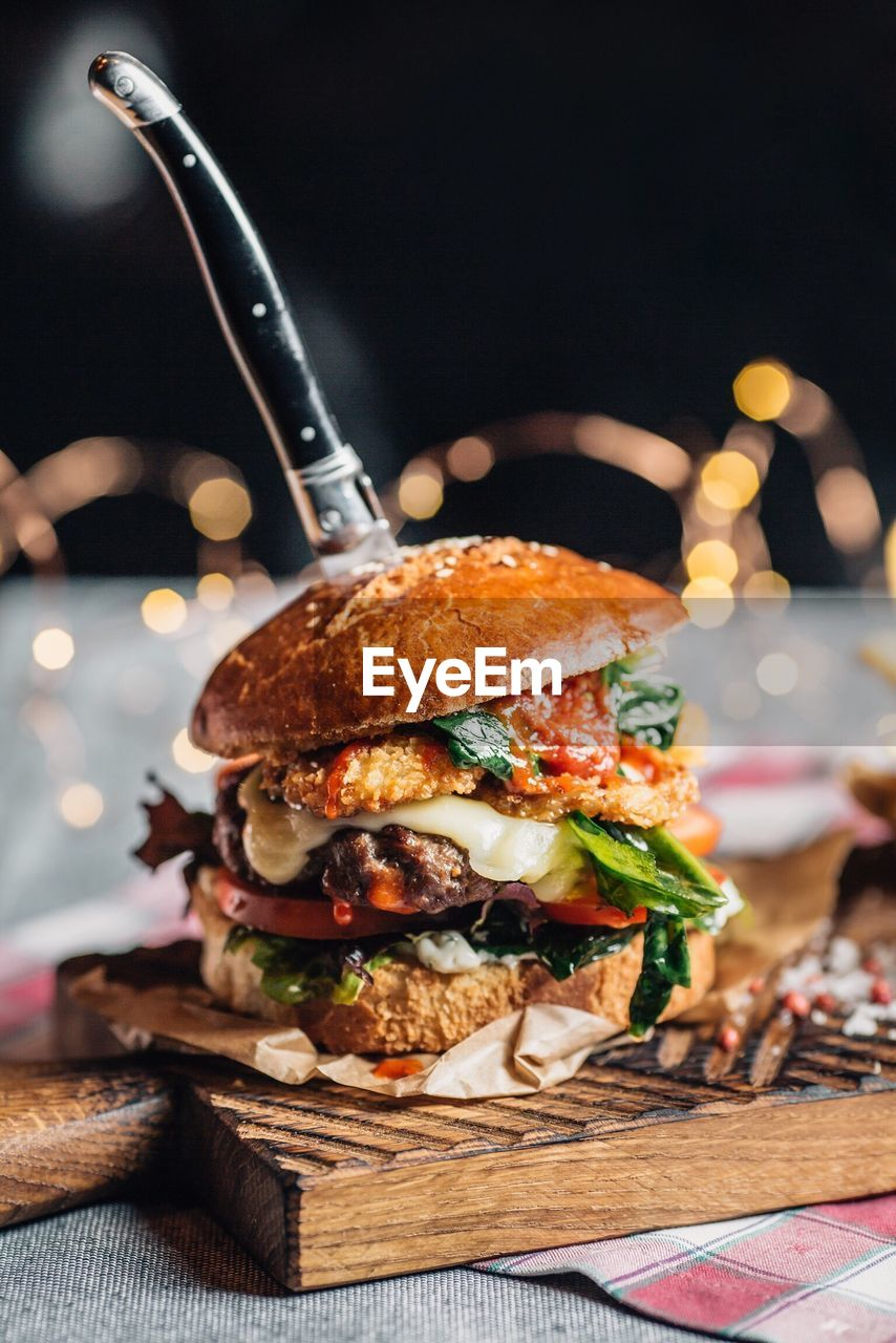 unhealthy eating, food, sandwich, fast food, food and drink, burger, ready-to-eat, focus on foreground, close-up, meat, freshness, indoors, bread, table, still life, no people, bun, serving size, vegetable, indulgence, hamburger, temptation, snack