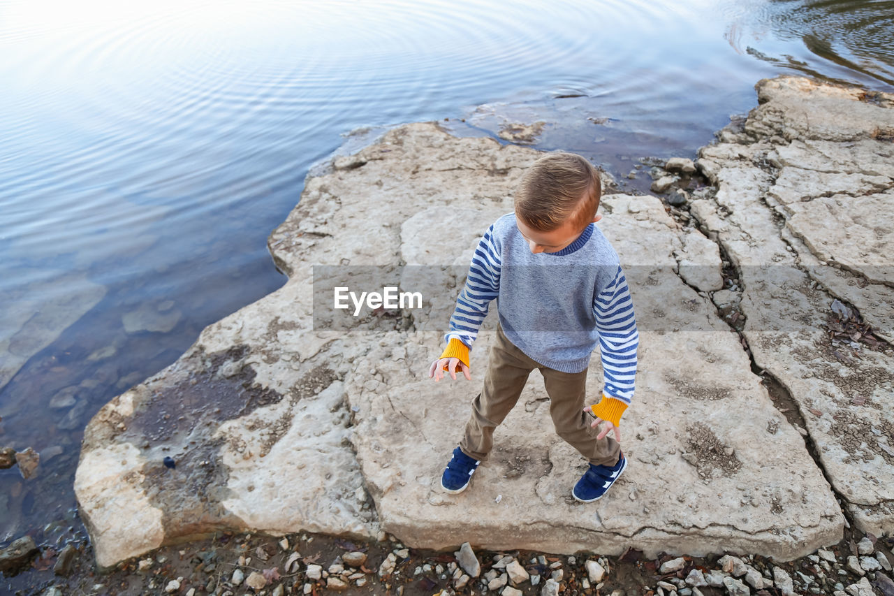 High angle view of boy dancing on rock at sea shore