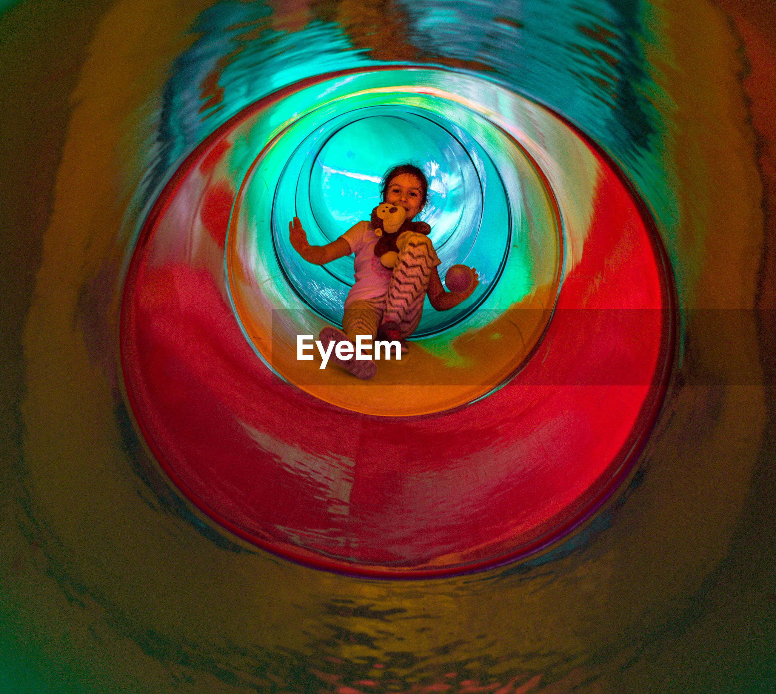 Full length portrait of girl in tunnel slide