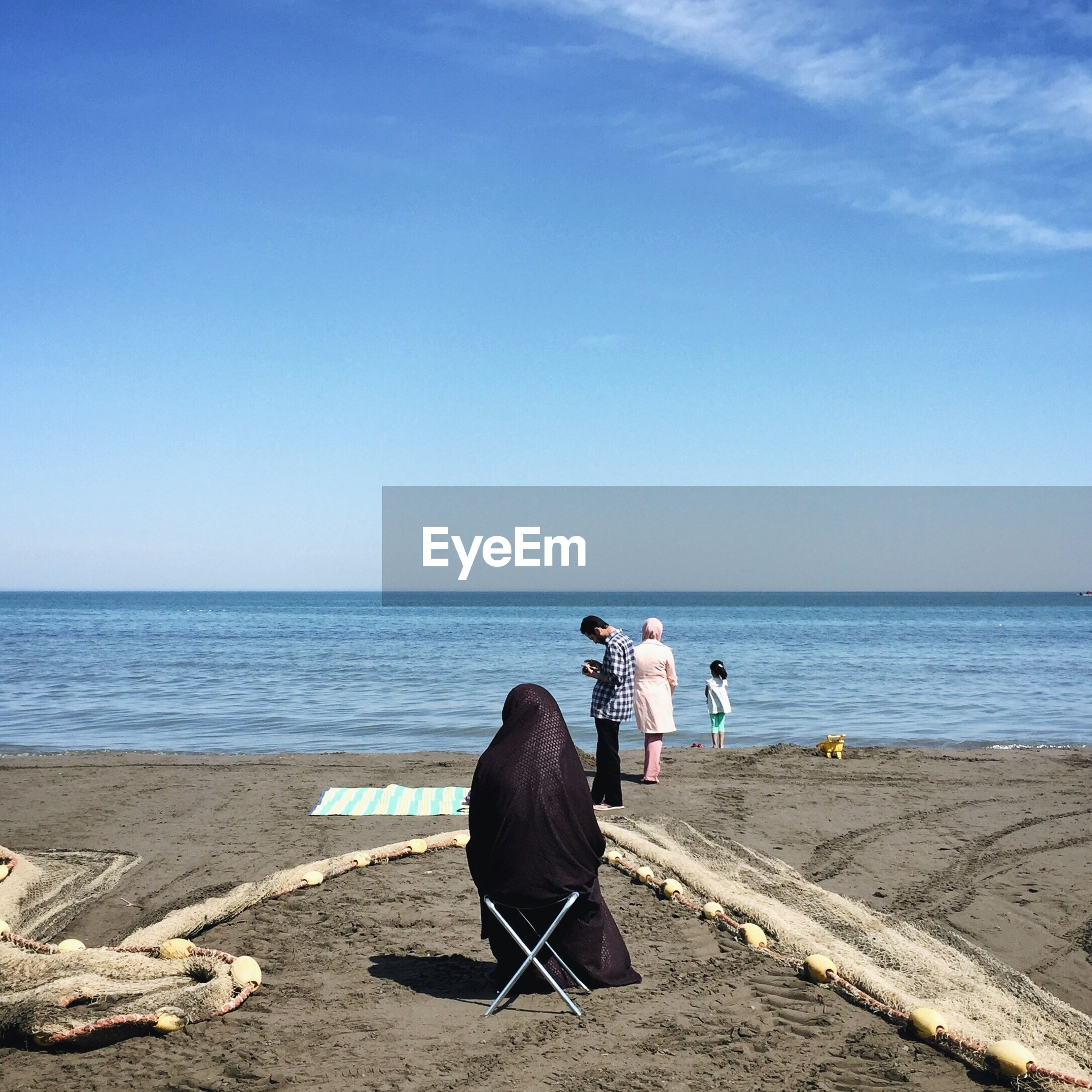 REAR VIEW OF MEN SITTING AT BEACH AGAINST CLEAR SKY