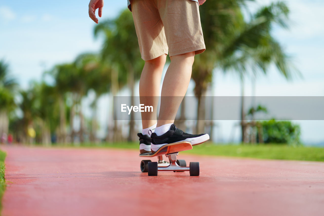Low section of person skateboarding on land