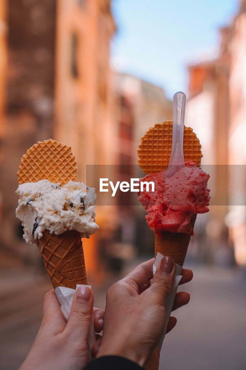 sweet food, sweet, human hand, ice cream, dairy product, frozen food, holding, food and drink, food, frozen, cone, unhealthy eating, hand, indulgence, ice cream cone, real people, temptation, dessert, focus on foreground, human body part, finger, outdoors, melting, human limb