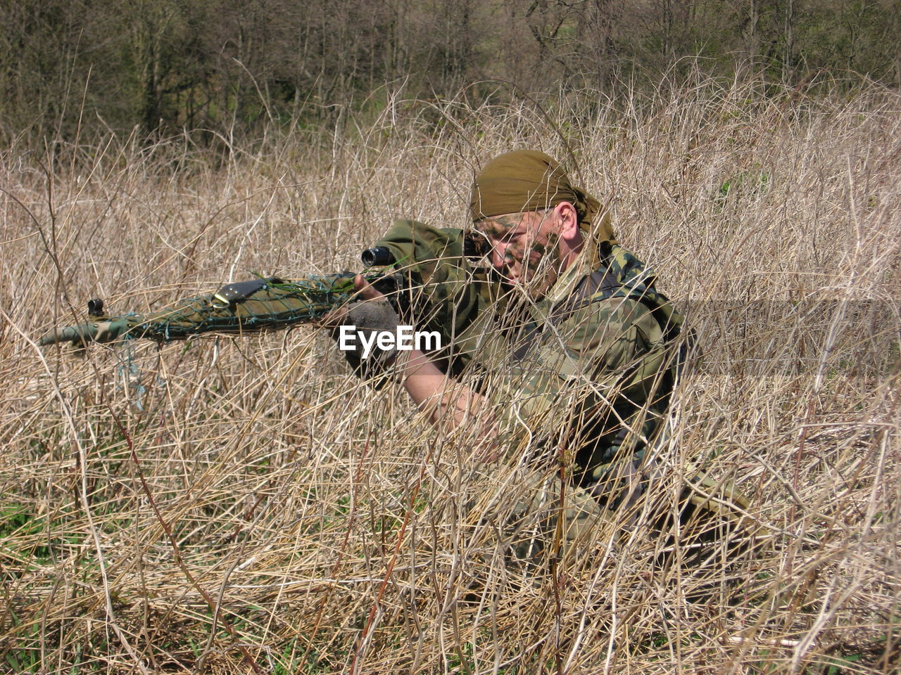 Sniped Aiming With Rifle At Grassy Field
