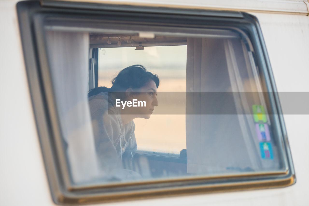 Woman In Camper Van Seen Through Window