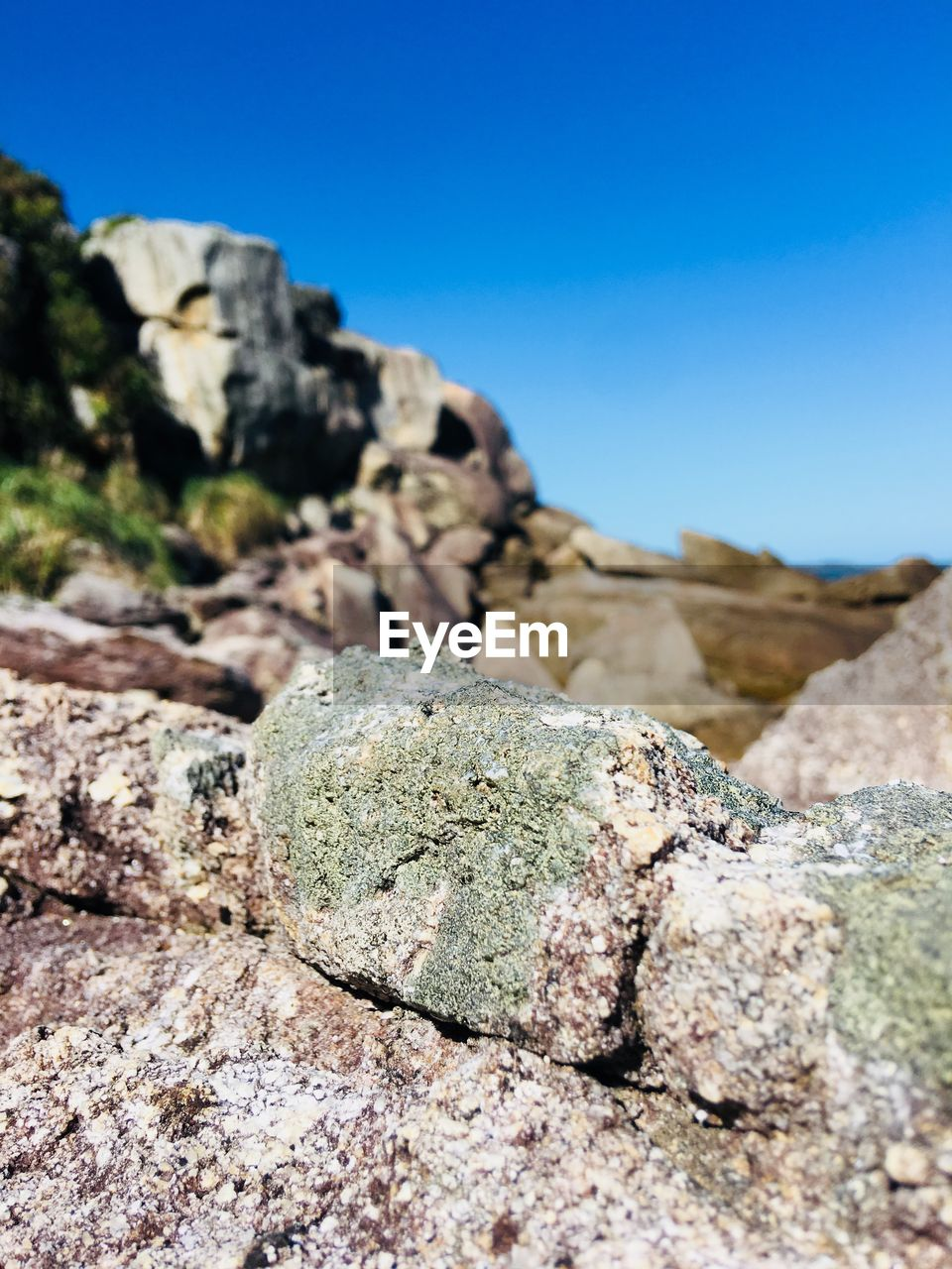 rock, solid, day, rock - object, sky, no people, nature, textured, focus on foreground, close-up, rough, blue, beauty in nature, tranquility, rock formation, outdoors, geology, sunlight, clear sky, selective focus