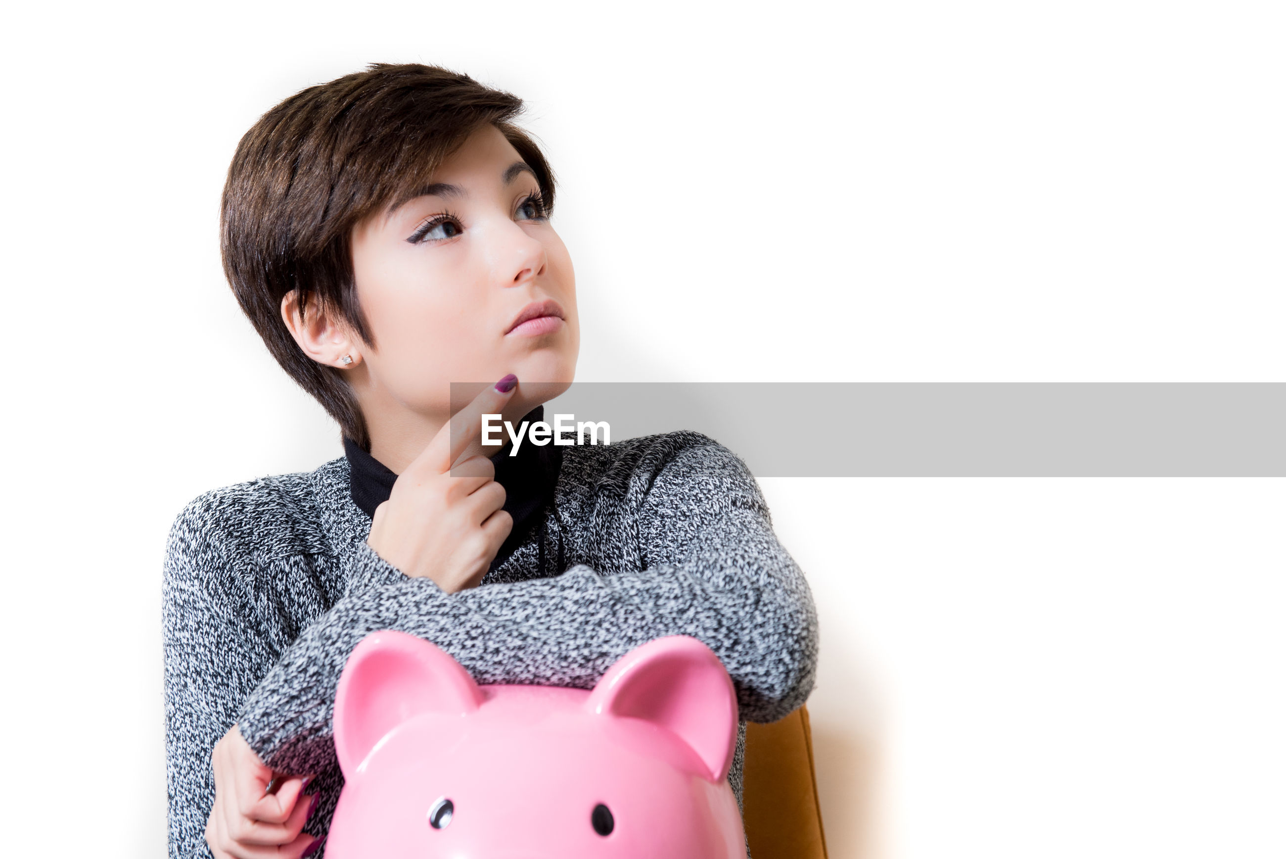 Thoughtful young woman holding pink piggy bank against white wall