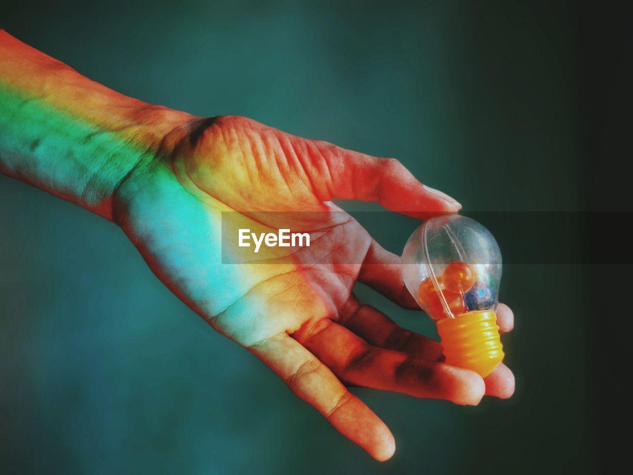 Close-Up Of Hand Holding Plastic Light Bulb