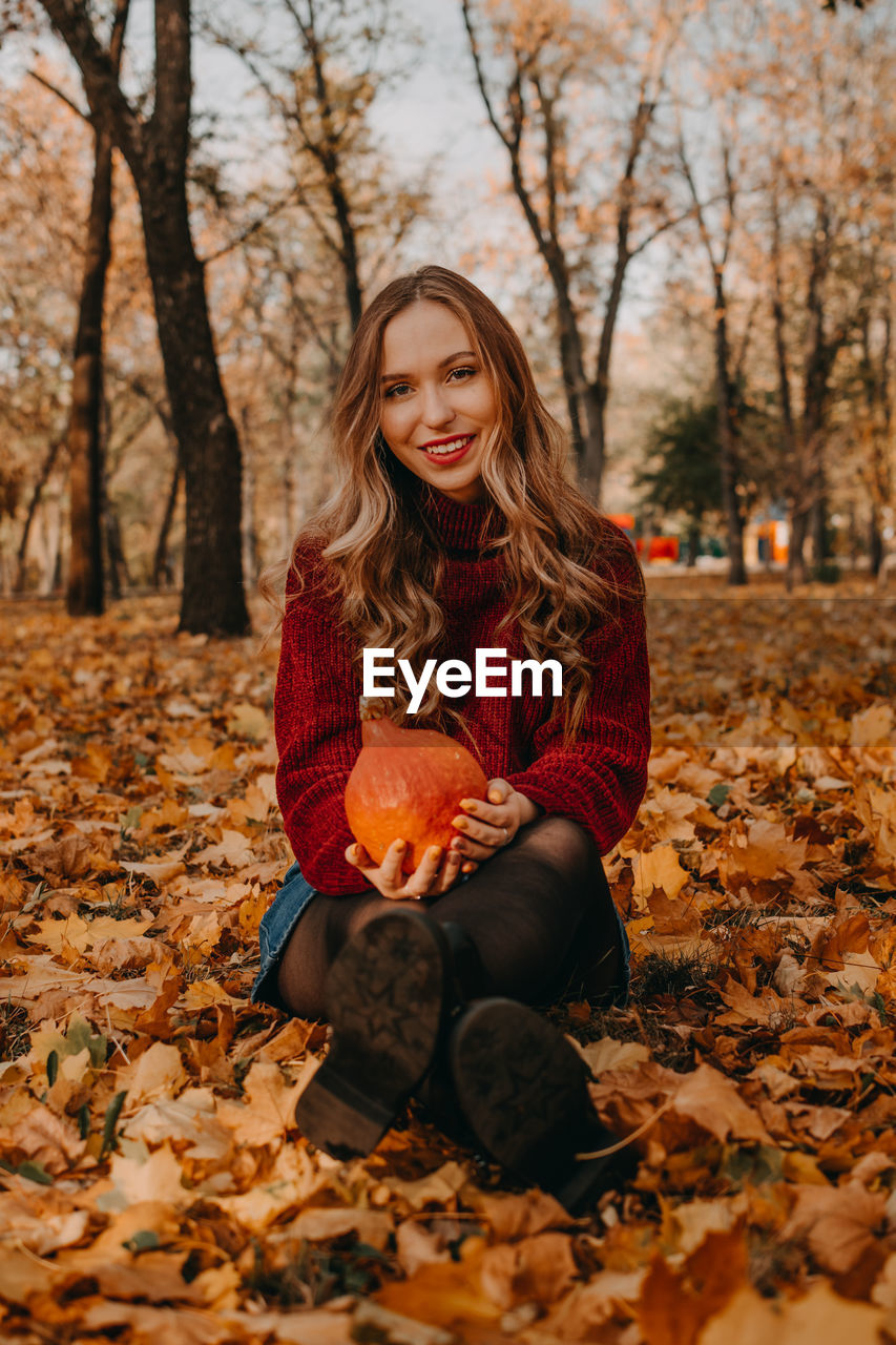 Portrait of beautiful woman sitting on tree during autumn