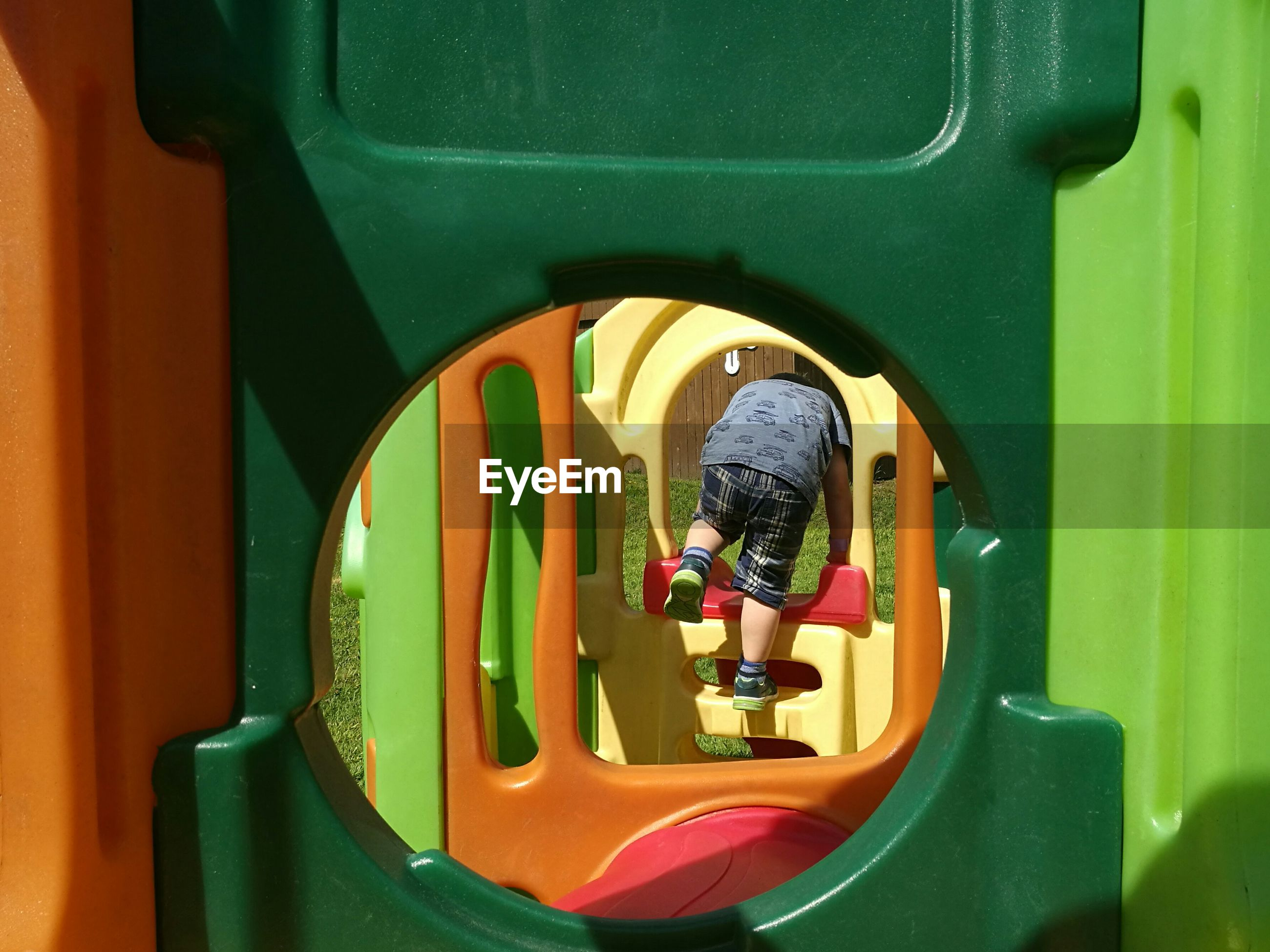Rear view of boy playing on jungle gym seen through hole