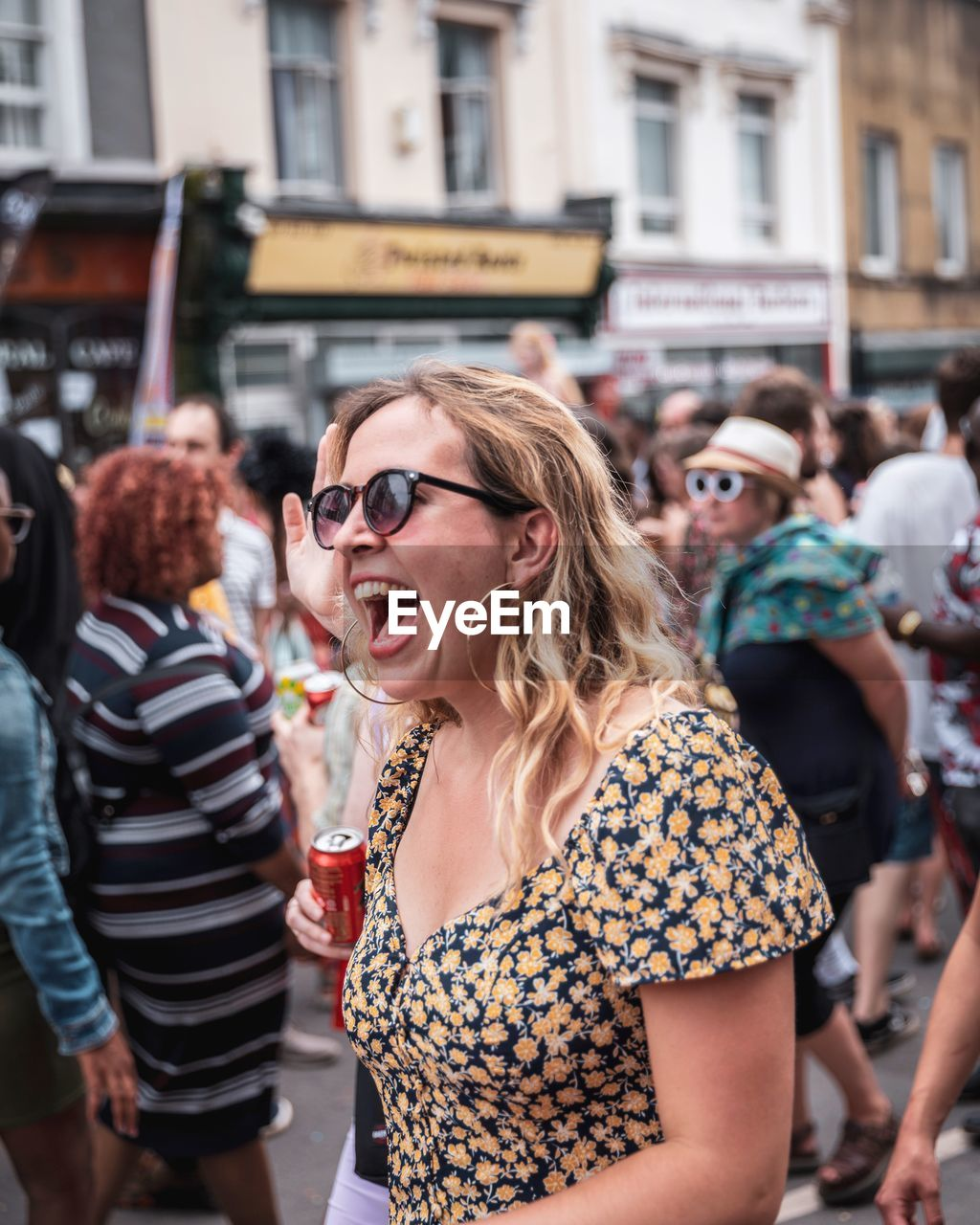 real people, lifestyles, young adult, leisure activity, glasses, focus on foreground, sunglasses, incidental people, people, adult, fashion, young women, group of people, event, women, city, mouth open, hairstyle, mouth, festival
