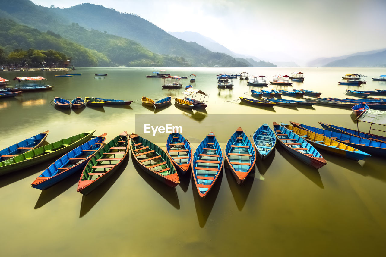 nautical vessel, water, transportation, mountain, nature, mode of transportation, day, scenics - nature, moored, beauty in nature, no people, tranquility, lake, outdoors, sky, in a row, mountain range, tranquil scene, multi colored, rowboat