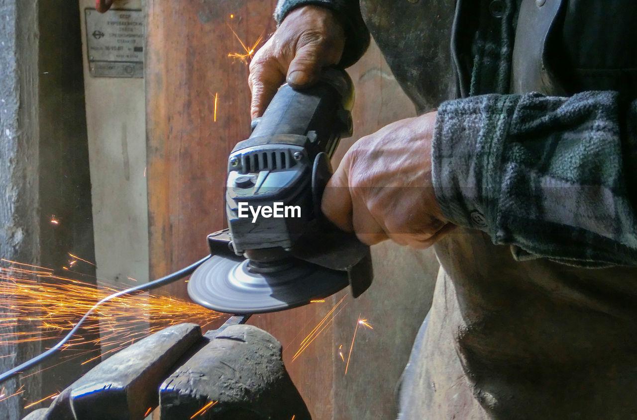 Midsection Of Blacksmith Molding Shape At Workshop