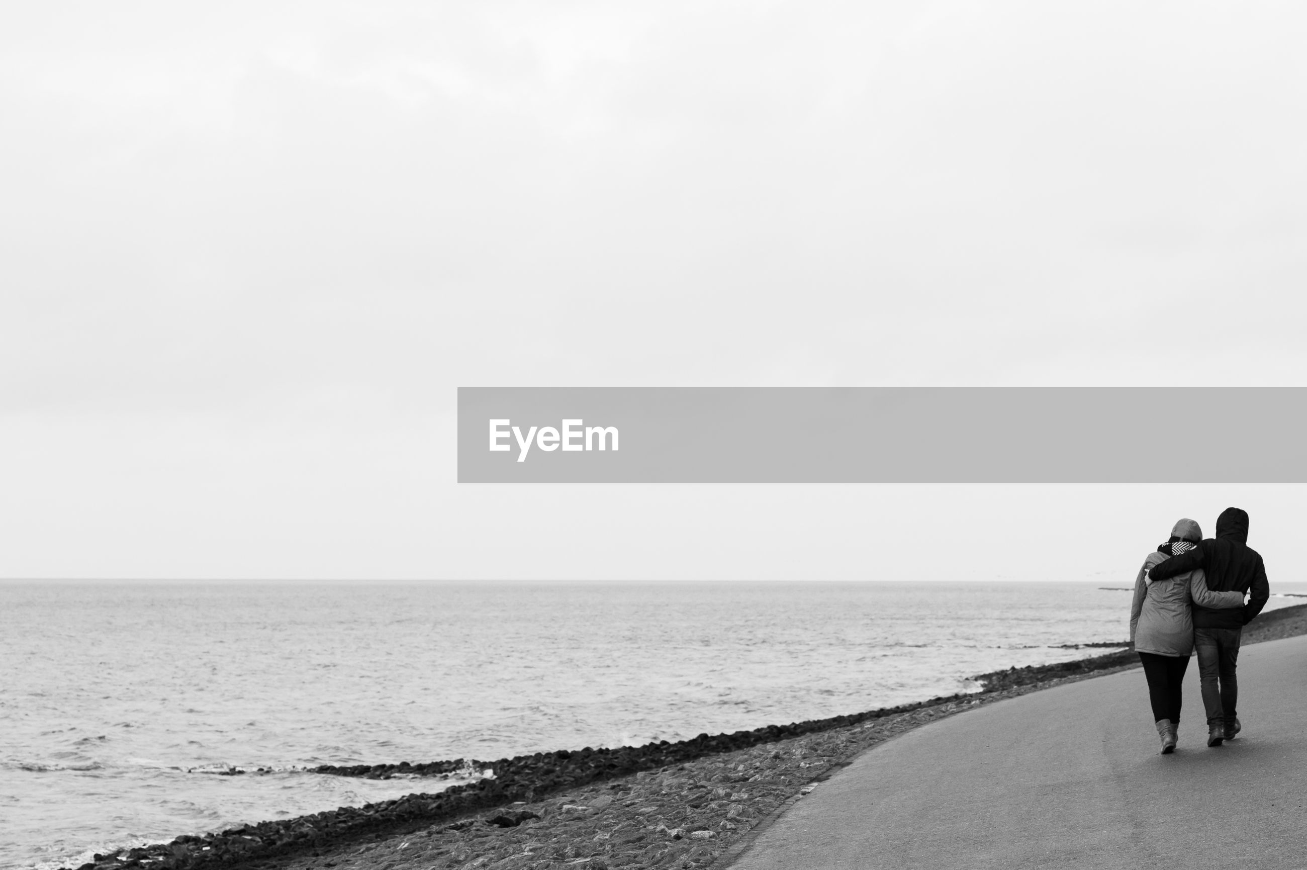 Rear view of couple walking on road by sea against clear sky