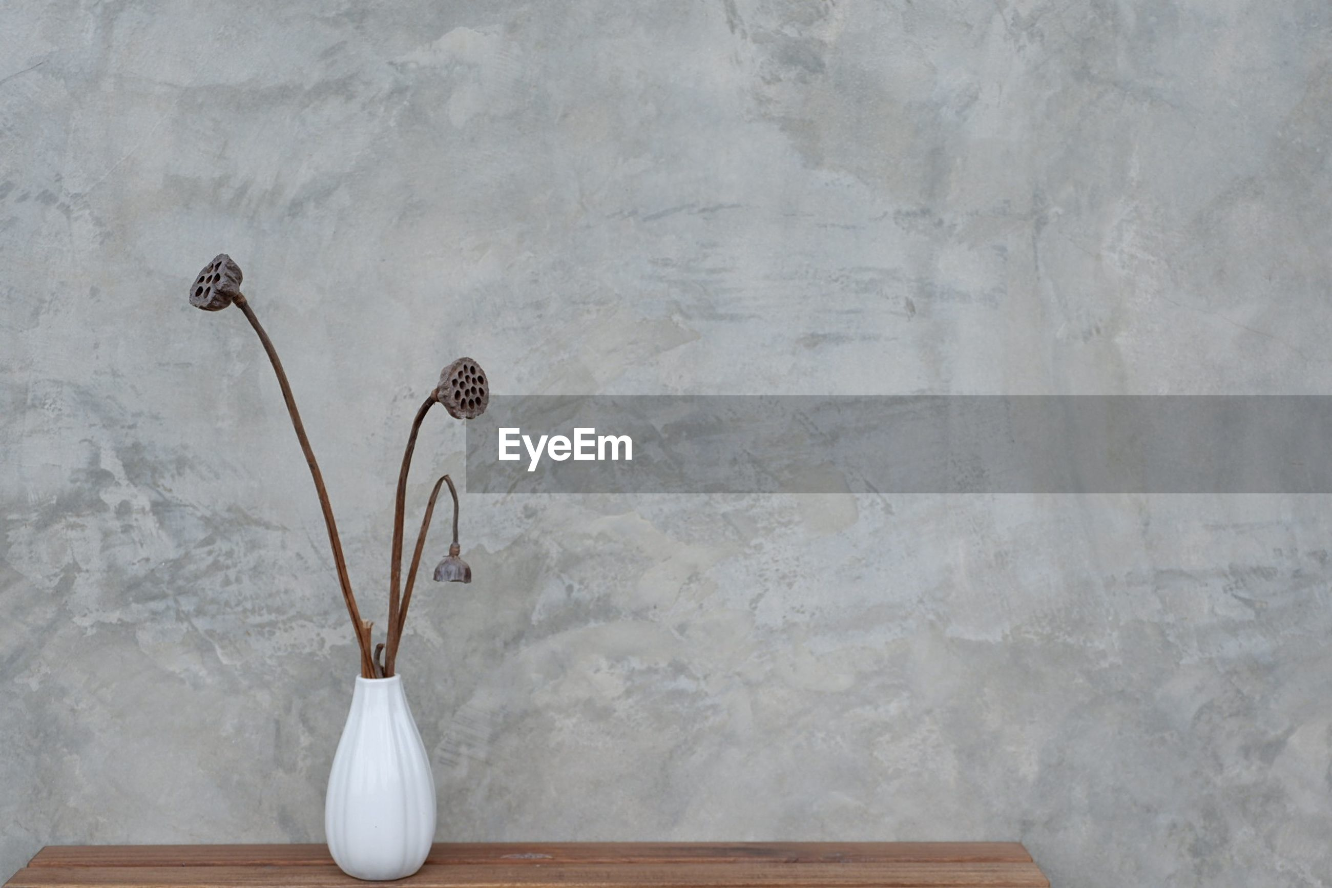 Close-up of white vase on table against wall