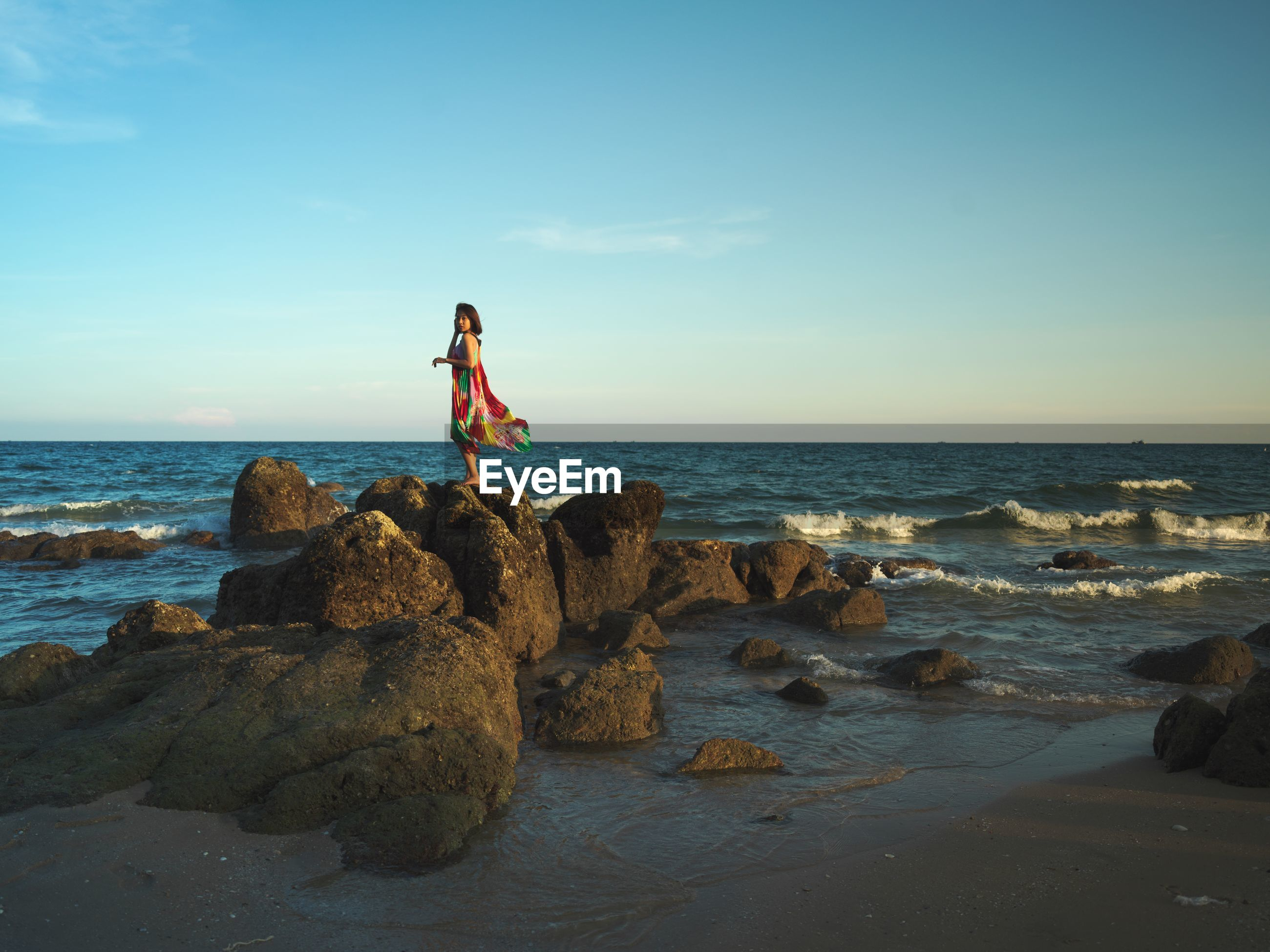 WOMAN STANDING ON ROCK AT SHORE AGAINST SKY