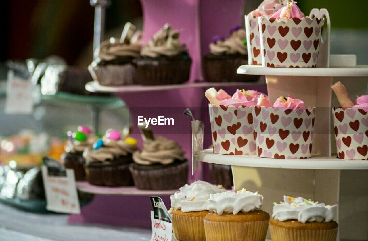 sweet food, cupcake, dessert, indulgence, food and drink, cake, freshness, temptation, food, sprinkles, still life, unhealthy eating, variation, indoors, no people, for sale, table, choice, wedding cake, store, ready-to-eat, focus on foreground, close-up, day, flower