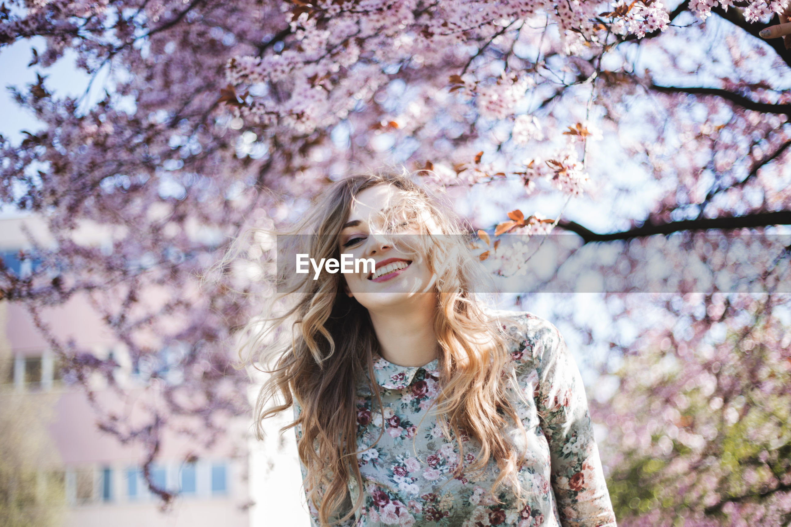PORTRAIT OF SMILING YOUNG WOMAN WITH CHERRY BLOSSOM