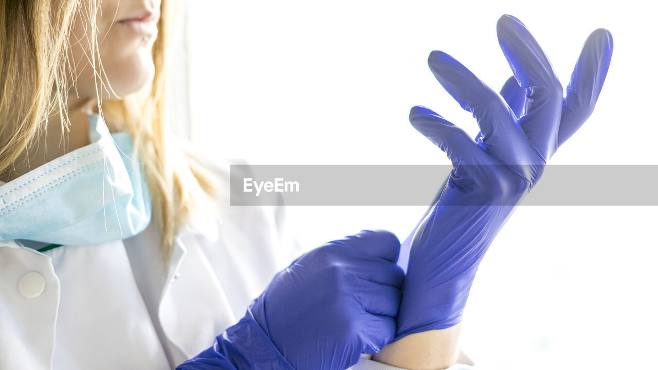 MIDSECTION OF WOMAN HOLDING HANDS AT BLUE