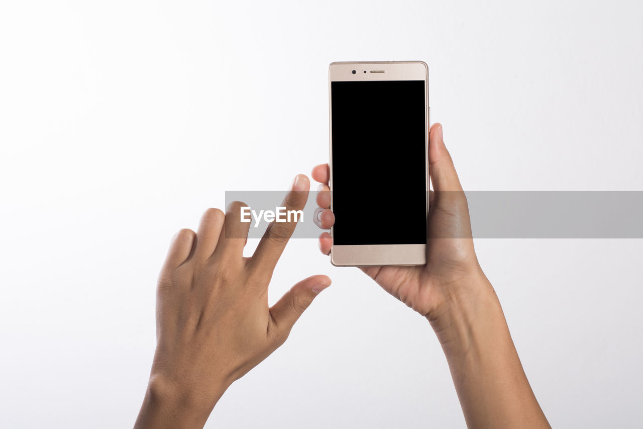 Close-up of human hand holding smart phone against white background