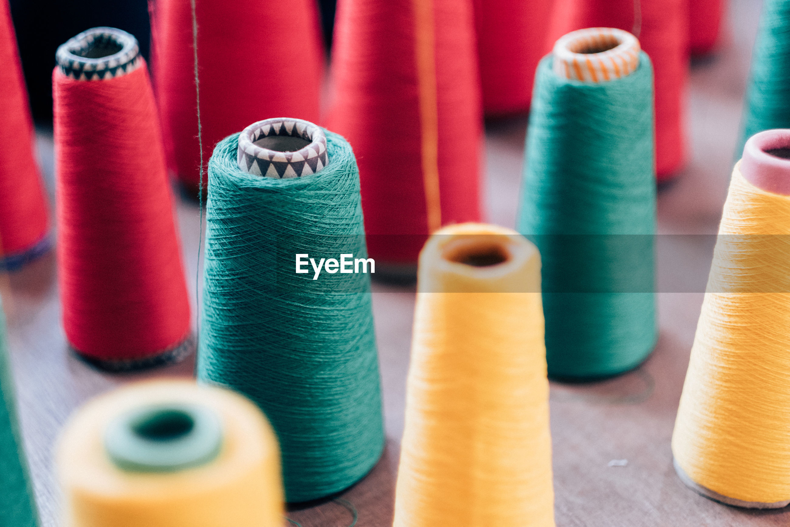 Close-up of colorful spools on wooden table