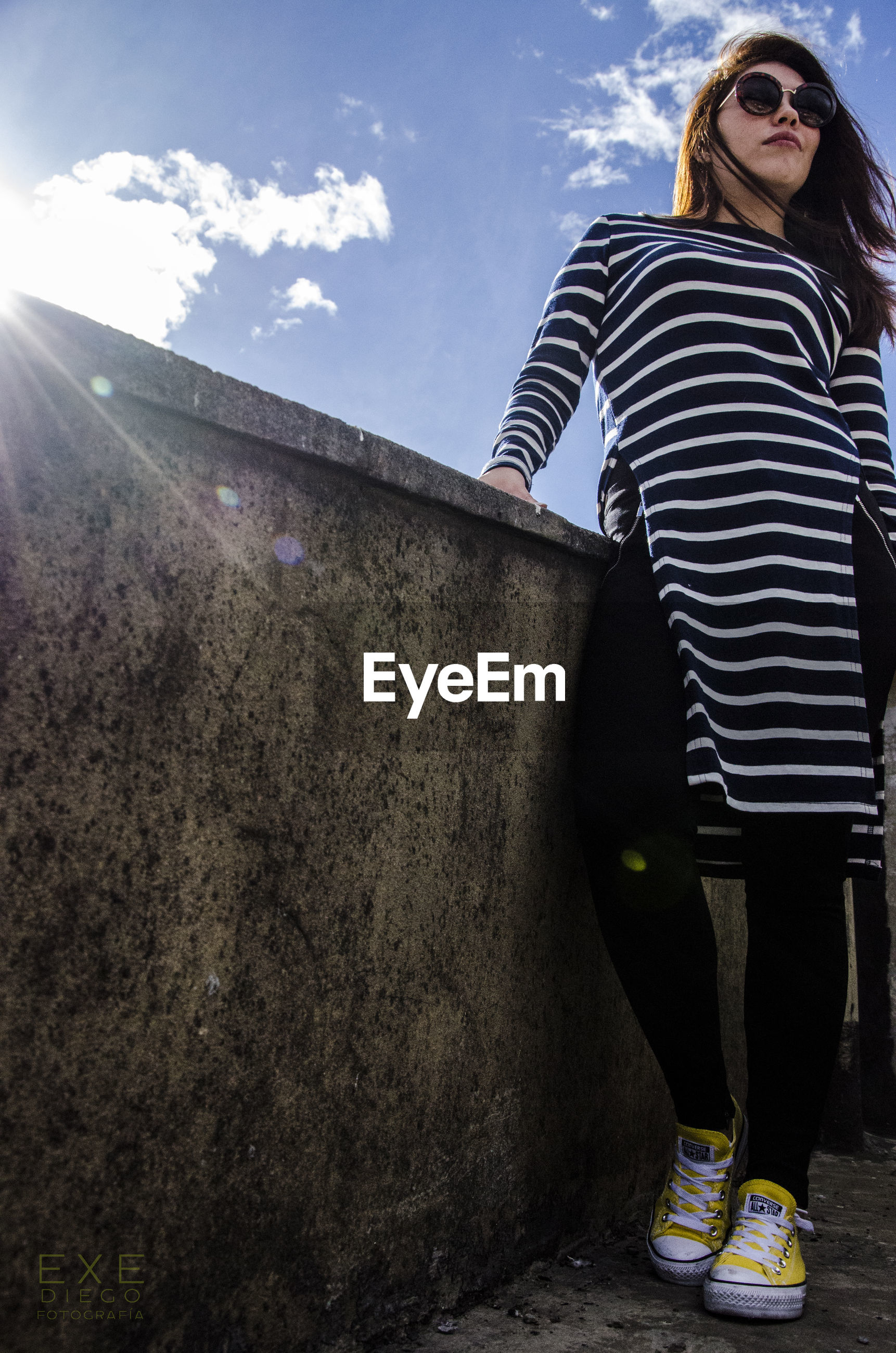 wall - building feature, low angle view, sky, standing, architecture, built structure, casual clothing, lifestyles, cloud, young adult, full length, person, contemplation, outdoors, well-dressed, day