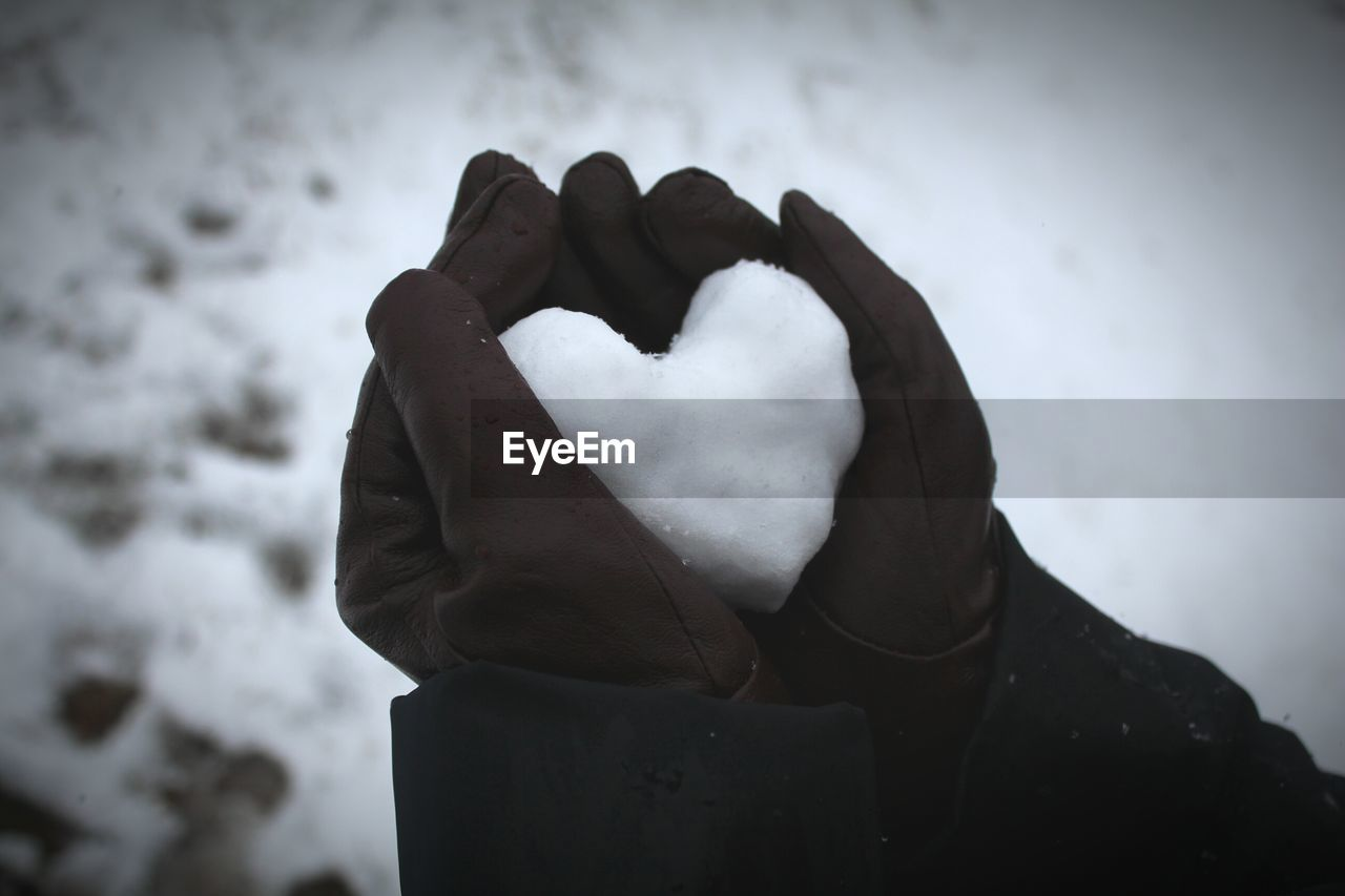 Close-up of person holding heart shaped snow
