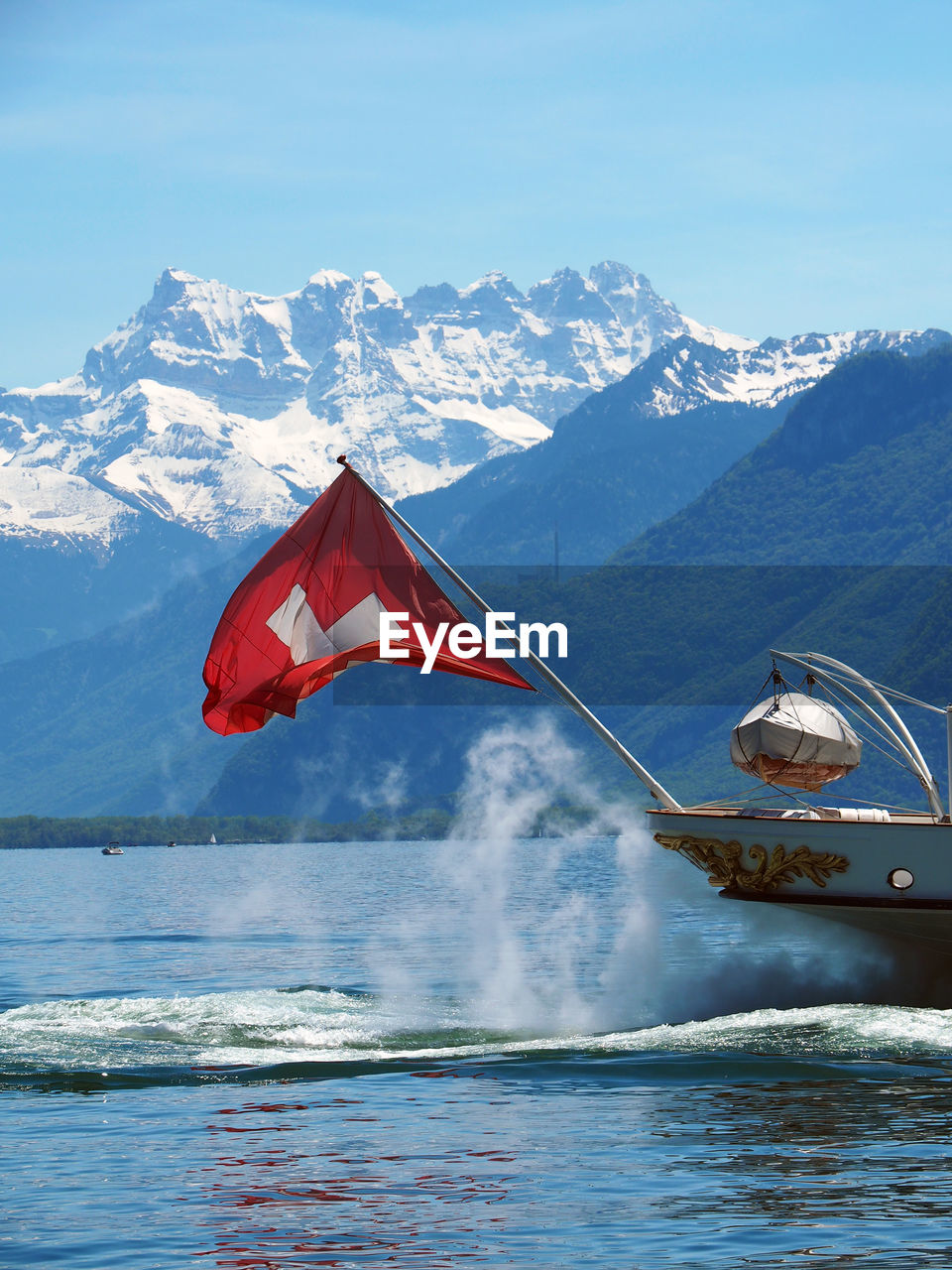 Swiss Flag On Passenger Craft Against Snowcapped Mountain