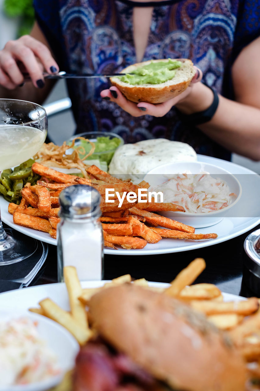 food and drink, food, real people, freshness, midsection, lifestyles, plate, human hand, selective focus, table, ready-to-eat, people, holding, unrecognizable person, hand, adult, women, human body part, close-up, meal