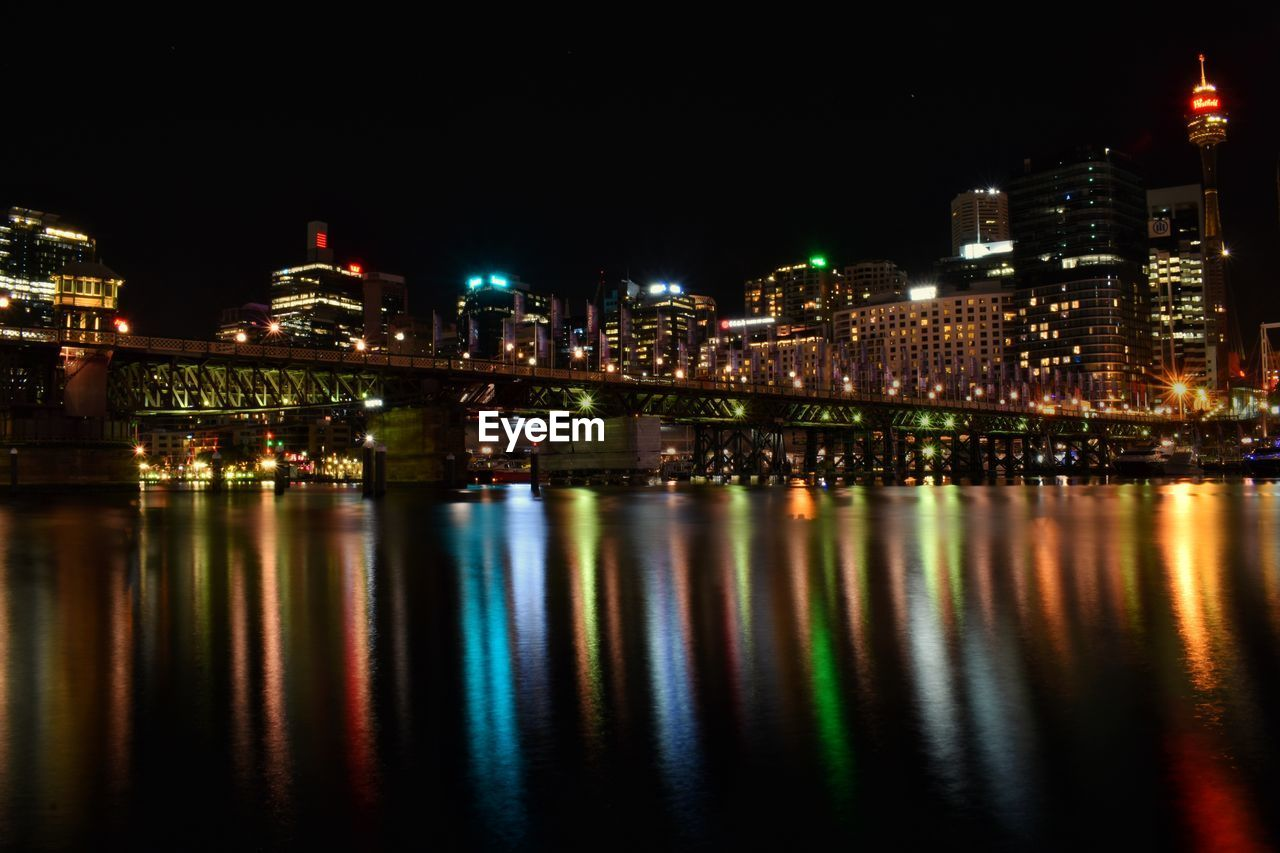 building exterior, illuminated, architecture, night, built structure, city, water, reflection, building, waterfront, no people, river, cityscape, nature, sky, connection, outdoors, travel destinations, office building exterior, skyscraper, nightlife, financial district