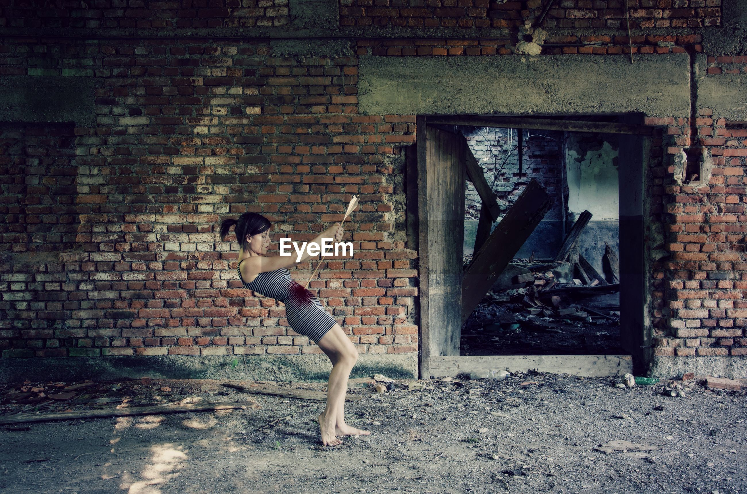 Digital compromise image of young woman killing herself with arrow by abandoned building