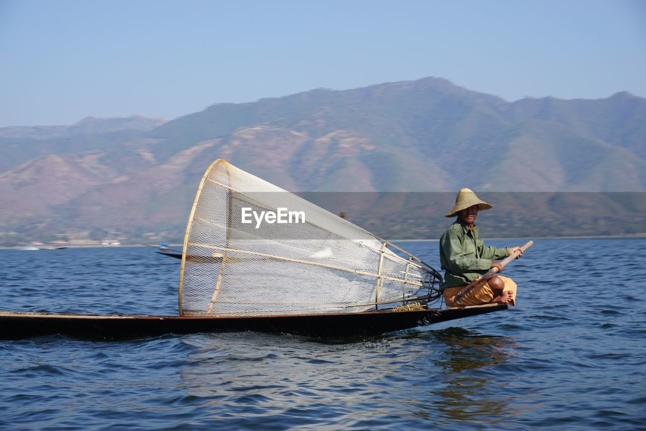 nautical vessel, transportation, boat, mode of transport, water, real people, mountain, outdoors, one person, nature, sailing, lake, fisherman, day, wooden raft, men, clear sky, oar, waterfront, scenics, occupation, standing, fishing net, full length, mountain range, sky, rowing, beauty in nature, people