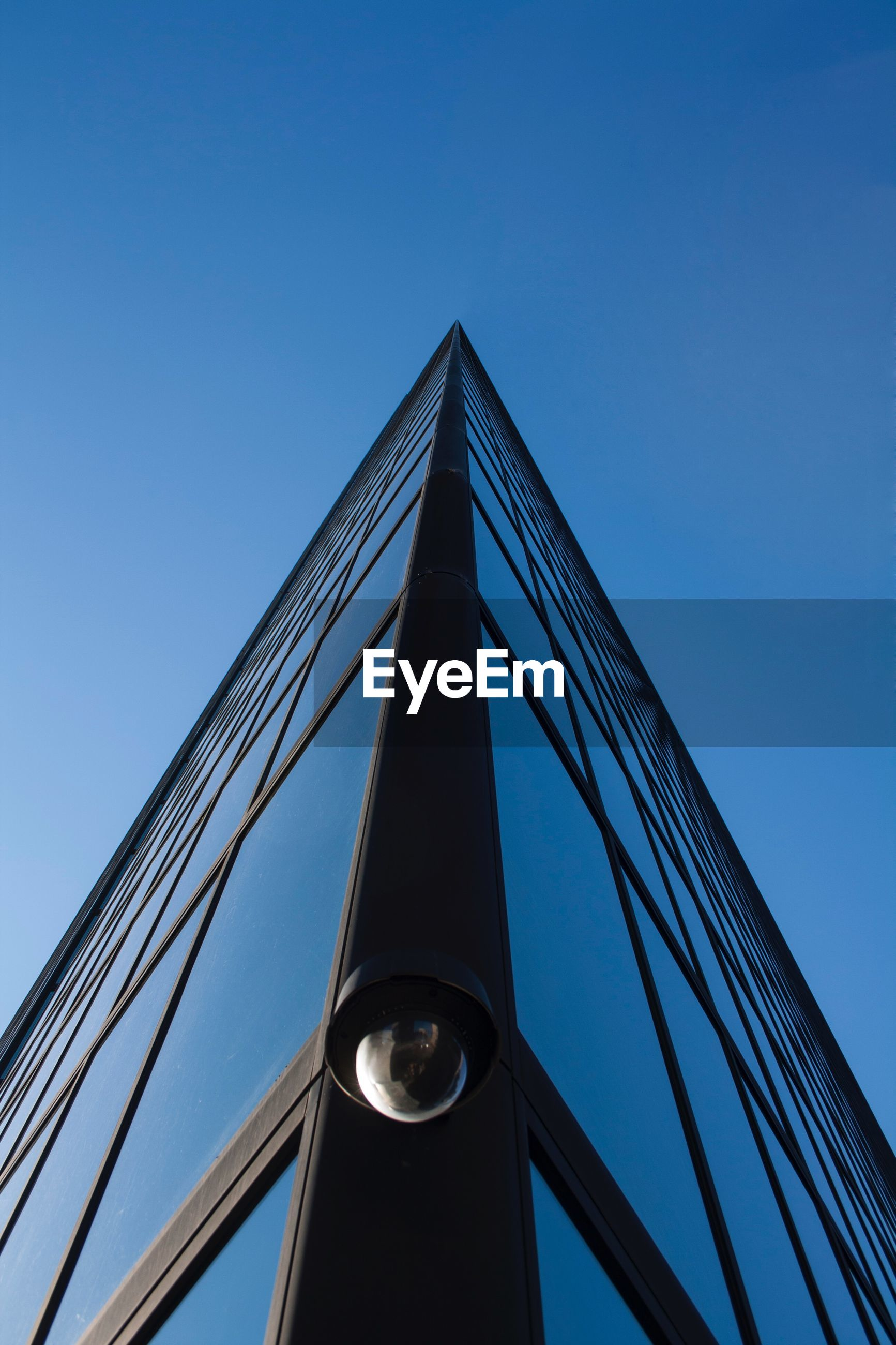 Low angle view of security camera on bridge against clear blue sky