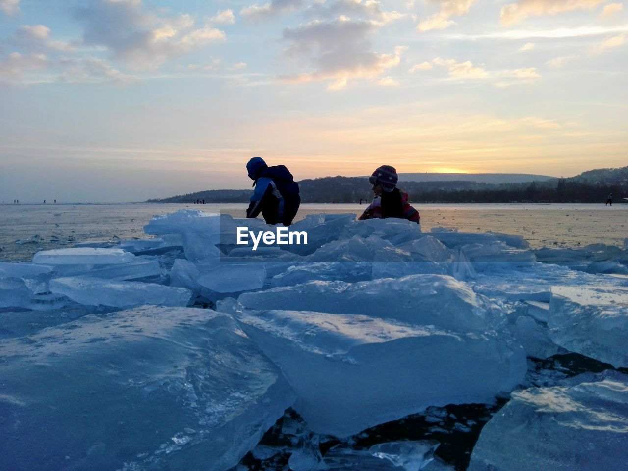 Siblings by ice formation against sky during sunset