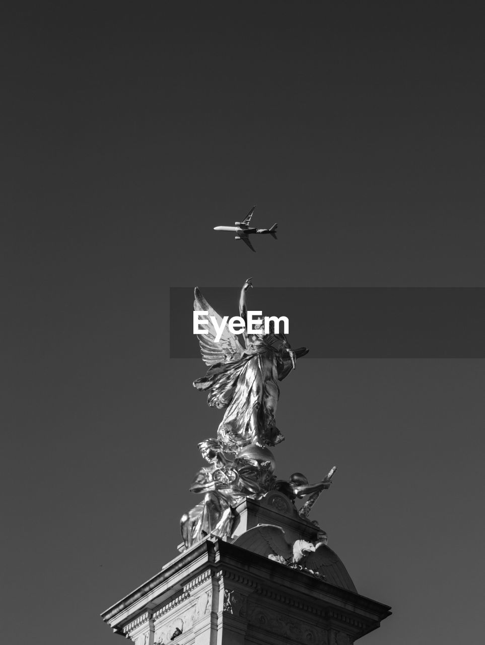 Low angle view of statue and airplane against sky