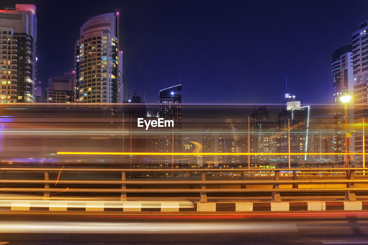 architecture, built structure, city, building exterior, night, illuminated, motion, long exposure, light trail, blurred motion, transportation, speed, building, sky, city life, road, no people, street, office building exterior, nature, outdoors, skyscraper, cityscape