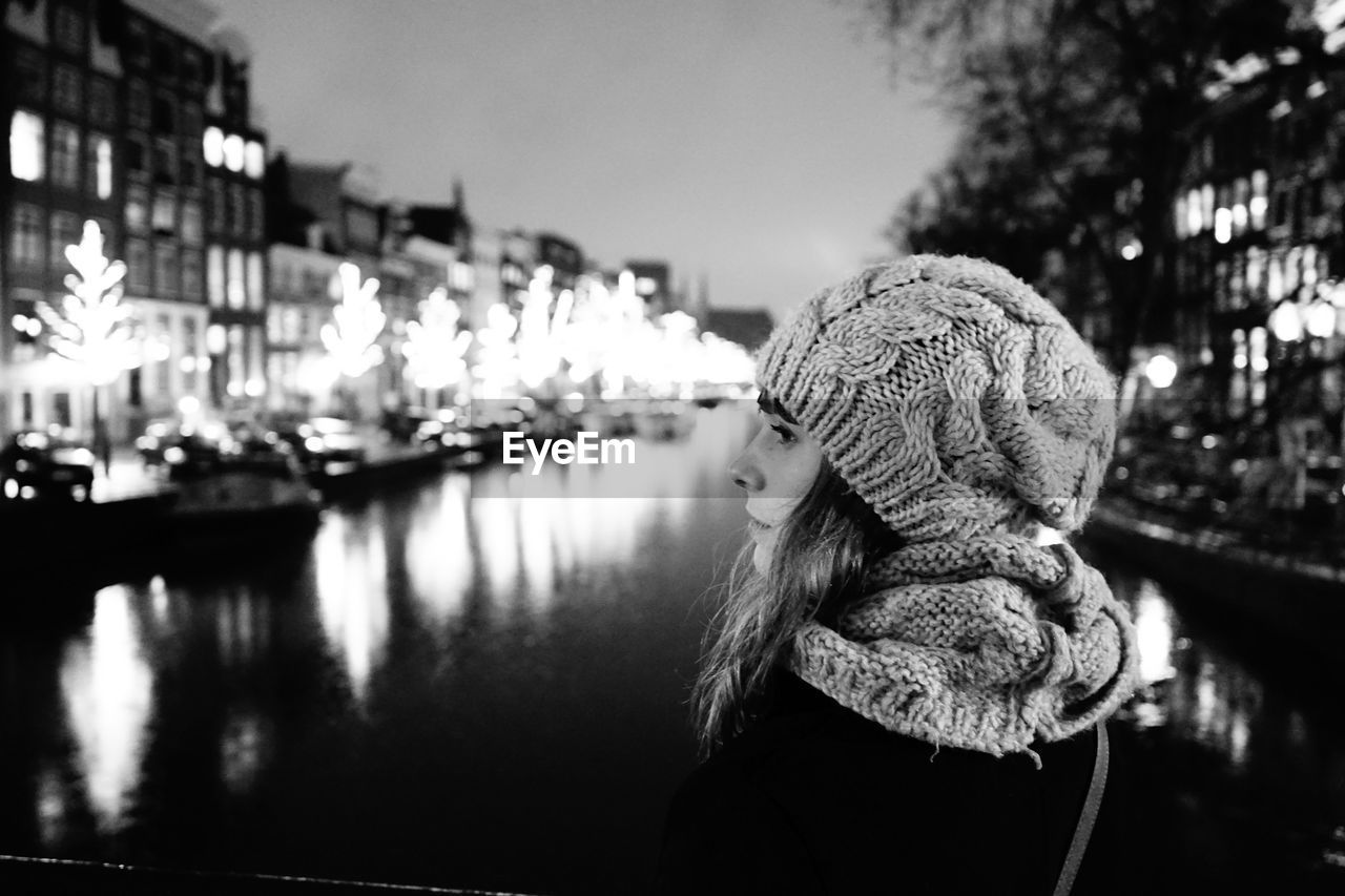 real people, focus on foreground, one person, knit hat, rear view, outdoors, warm clothing, leisure activity, building exterior, water, day, close-up, people