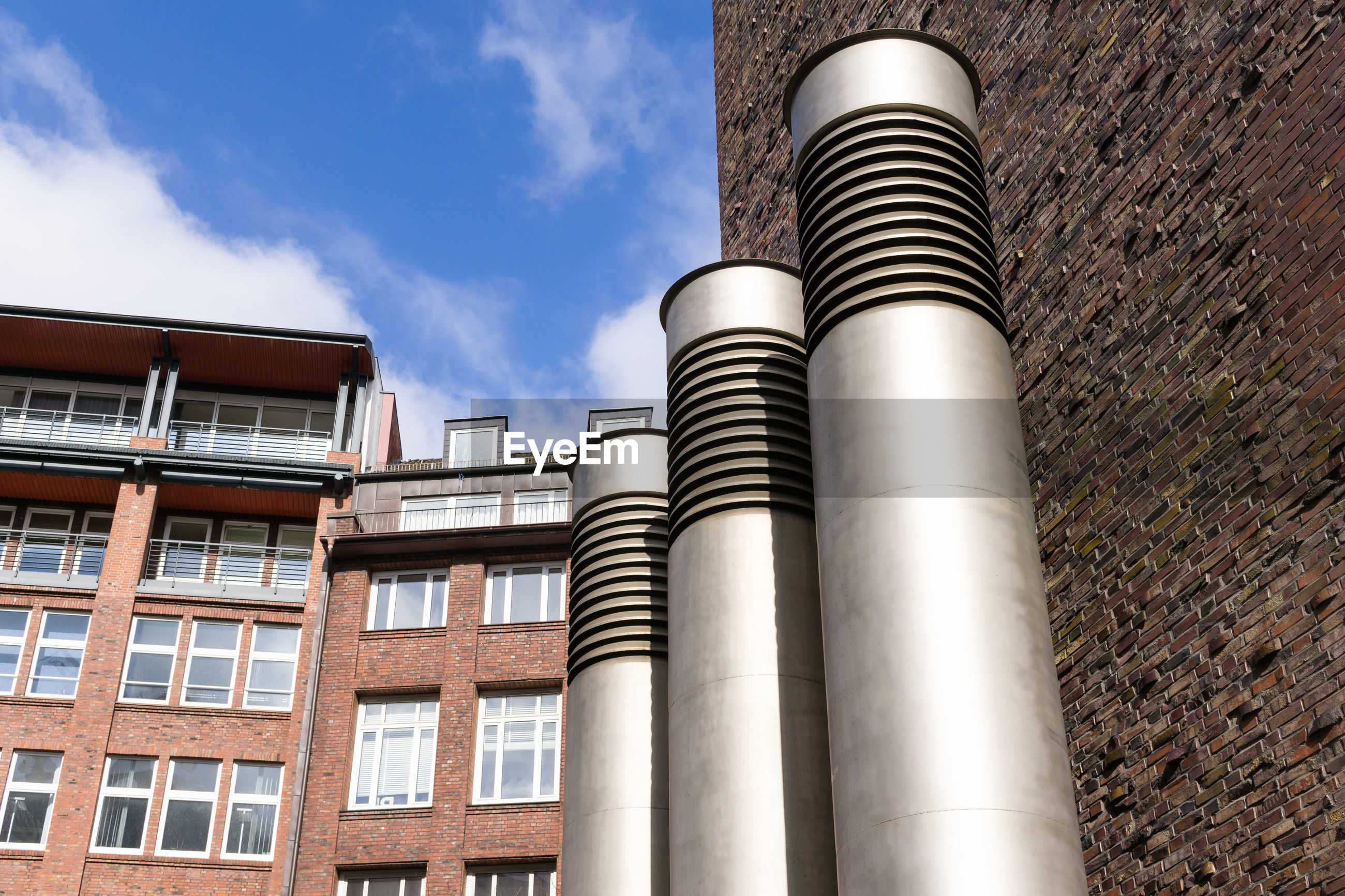 Low angle view of ventilation pipes against old building