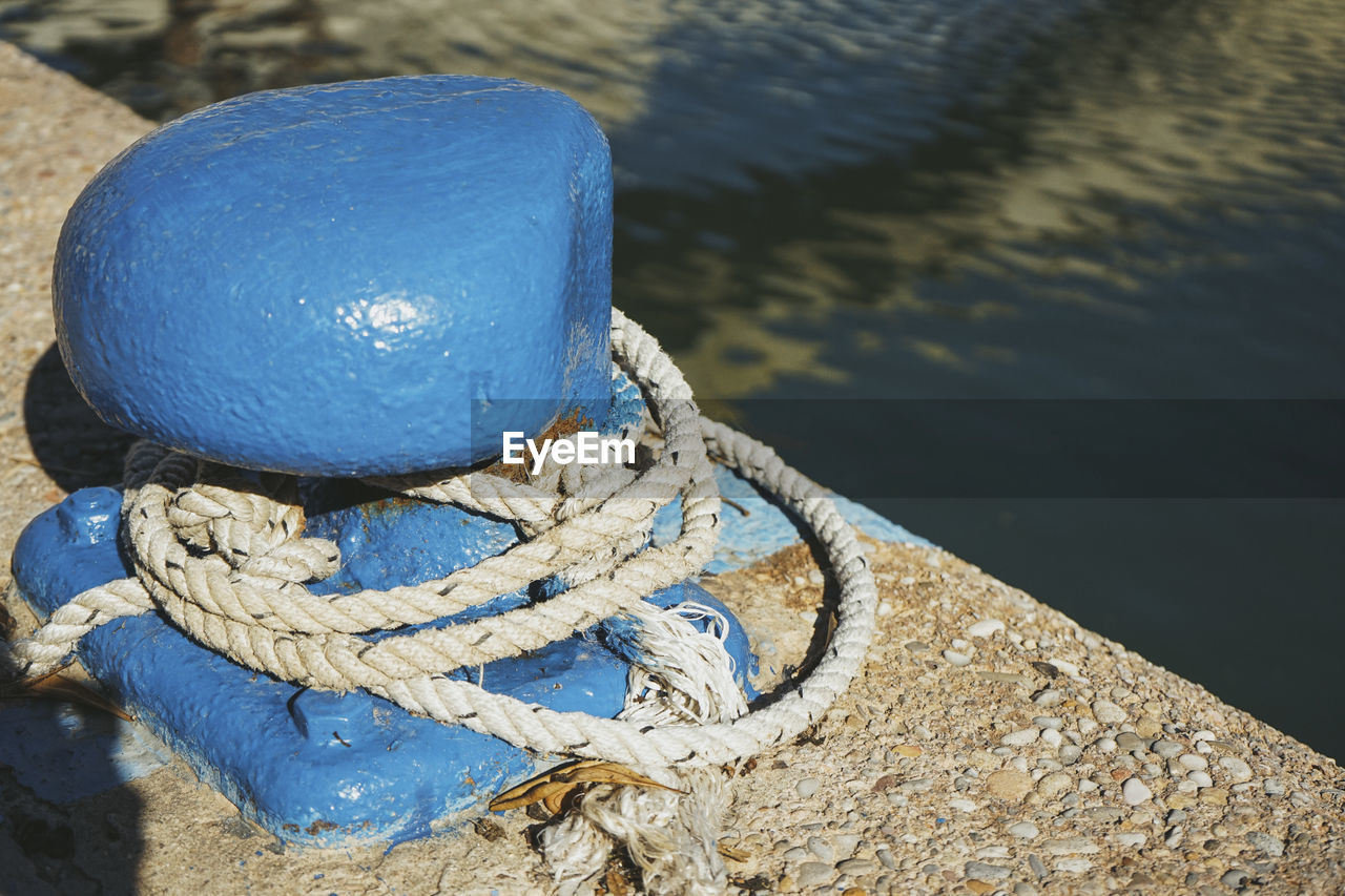 HIGH ANGLE VIEW OF ROPE TIED TO BOAT