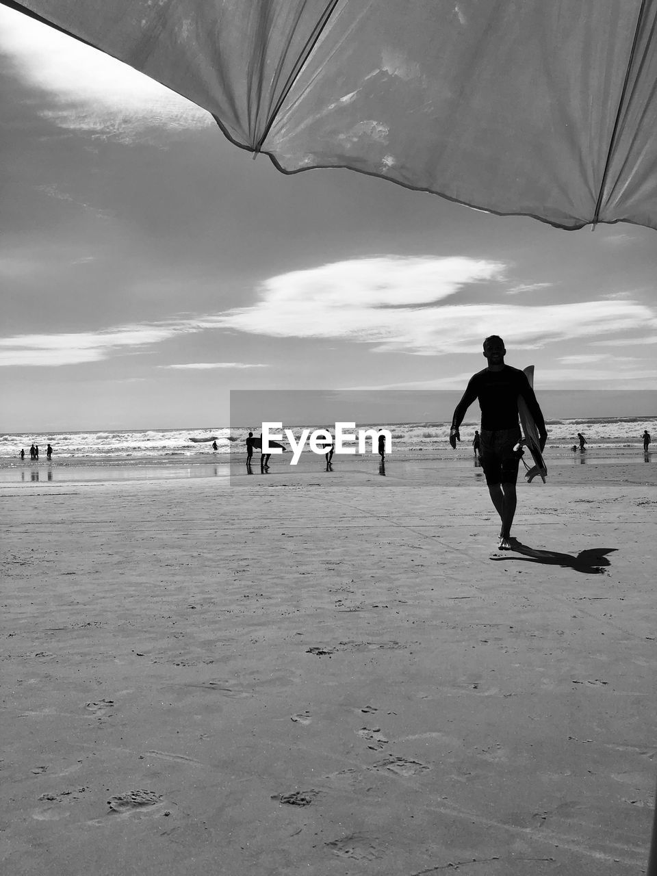 Man with surfboard walking at beach against sky