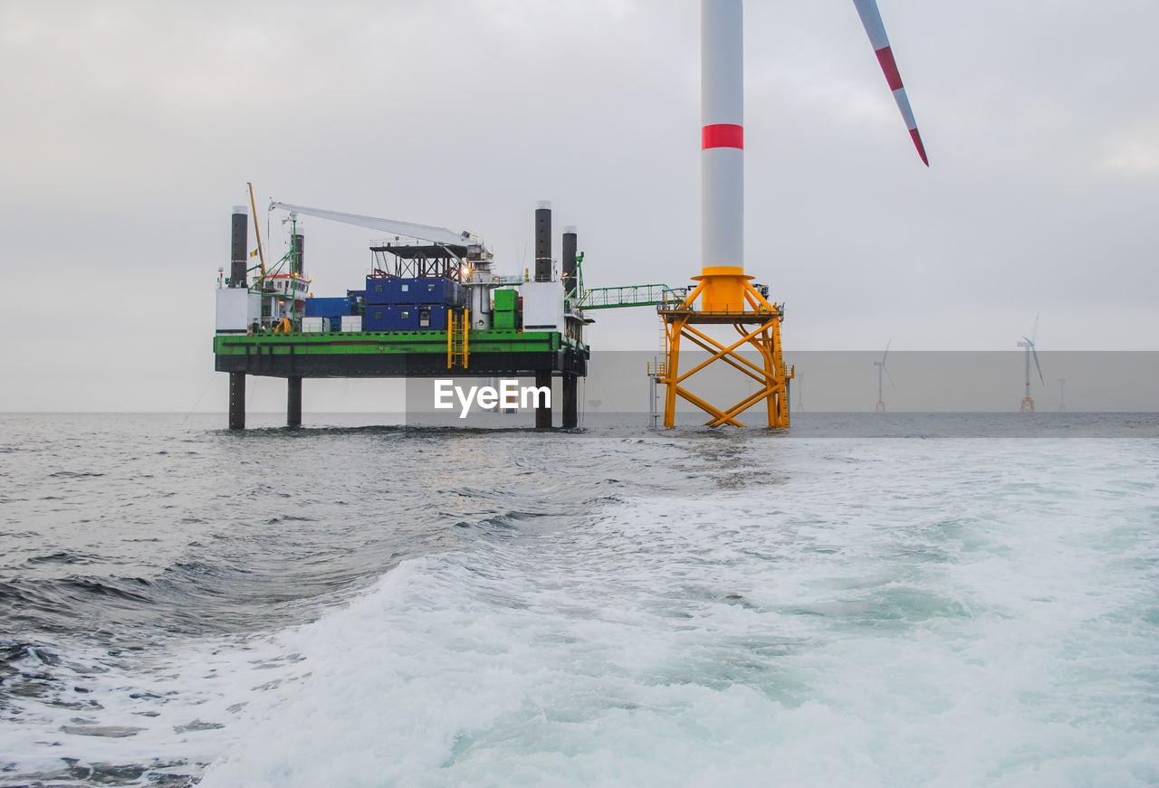 Offshore Platform By Wind Turbine In Sea Against Sky