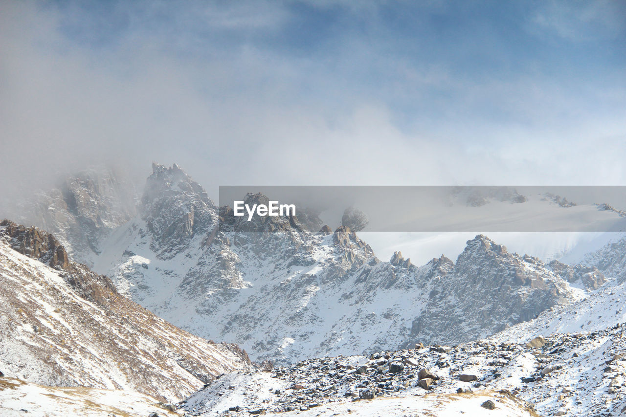 Peaked rocky snow-capped ridge peaks in cloudy fog in tuyuk-su gorge in sunny winter weather