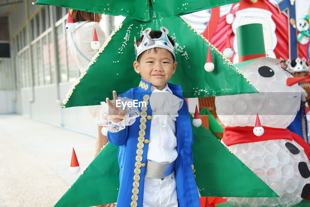 Portrait of smiling boy wearing crown while standing by christmas tree in party