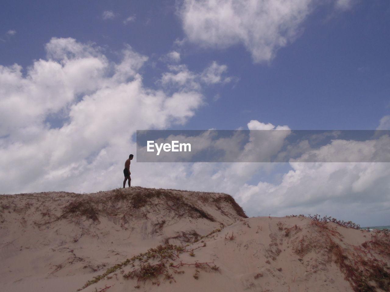 Man Standing On Sand Dune At Desert Against Sky