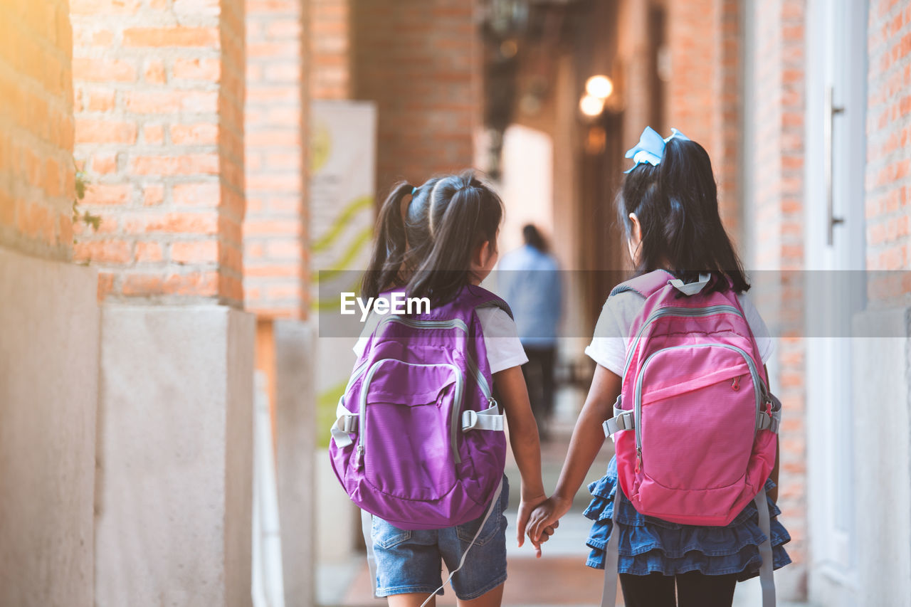 women, girls, child, architecture, real people, childhood, females, three quarter length, casual clothing, togetherness, rear view, two people, standing, family, walking, people, building exterior, built structure, backpack, lifestyles, hairstyle, sister, outdoors