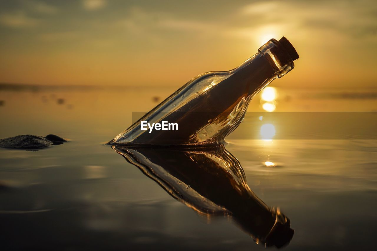 Close-up of bottle floating on water against sunset sky