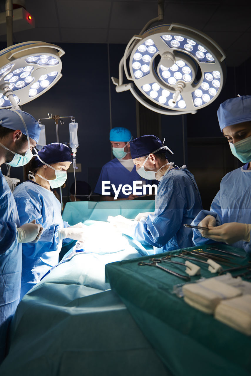 group of people, occupation, men, adult, operating room, indoors, cooperation, surgeon, teamwork, expertise, surgical cap, women, males, doctor, surgical mask, people, real people, waist up, standing, working, skill, coworker, mature men, responsibility, scrubs, uniform, surgical equipment