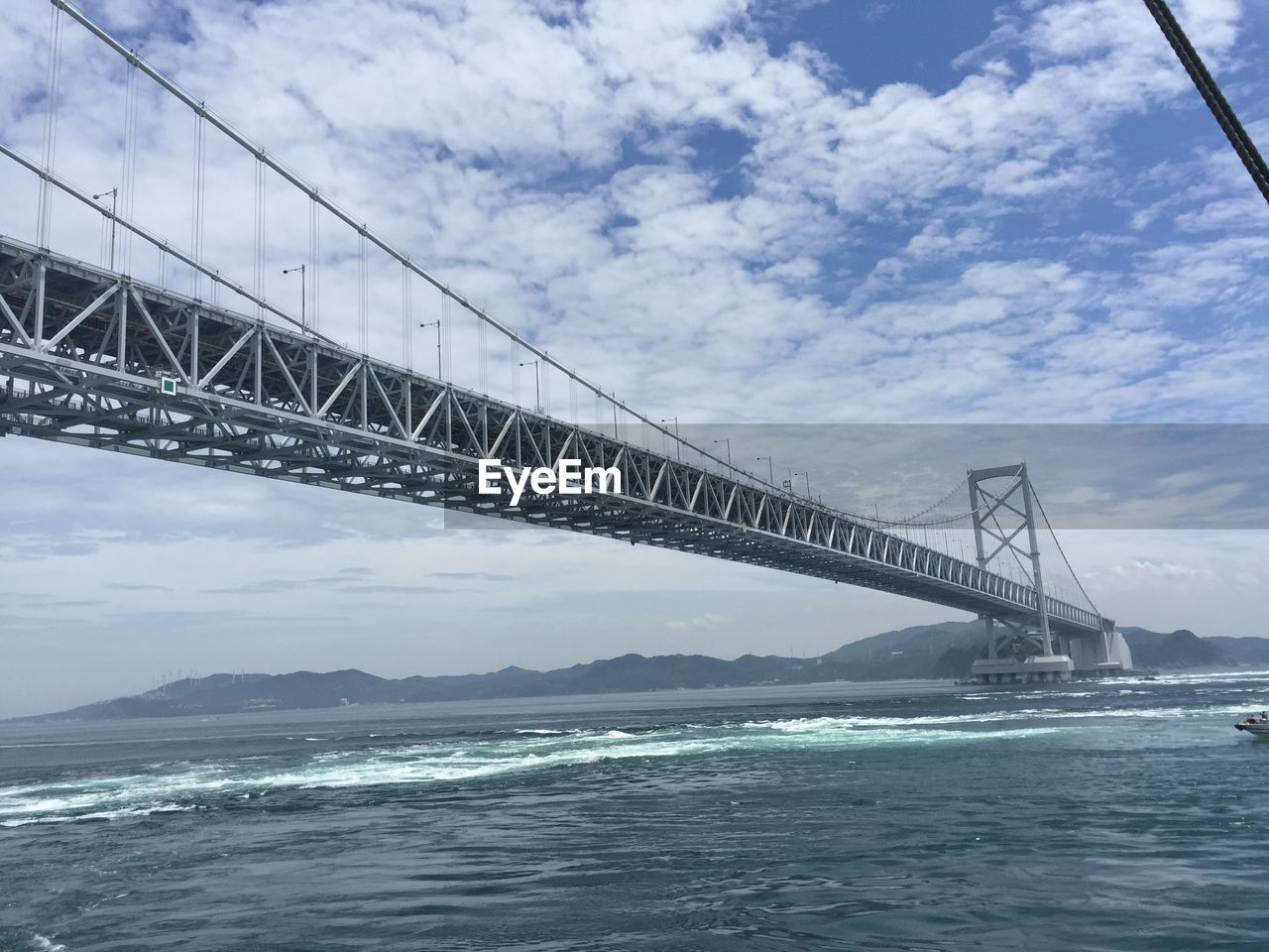 bridge - man made structure, connection, suspension bridge, sky, transportation, architecture, engineering, cloud - sky, travel destinations, built structure, water, sea, outdoors, tourism, travel, no people, day, nature, bridge, beauty in nature, mountain, city