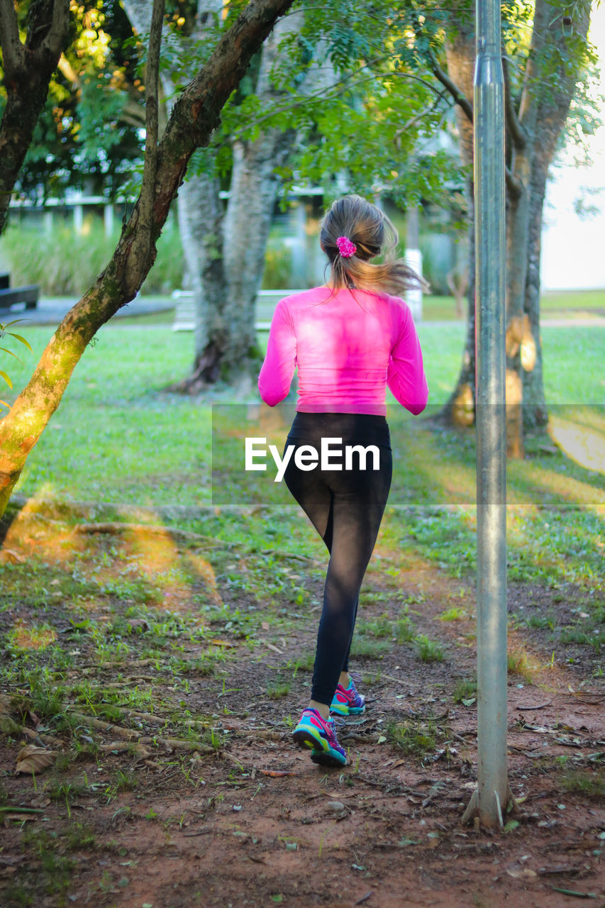 Rear view of young woman running against trees at park