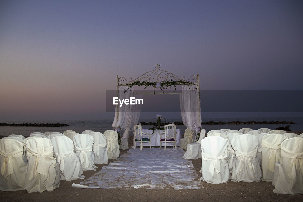 wedding, sea, horizon over water, celebration, sky, bride, clear sky, life events, chair, beach, water, wedding ceremony, ceremony, outdoors, nature, scenics, beauty in nature, wedding dress, day, bridegroom, people